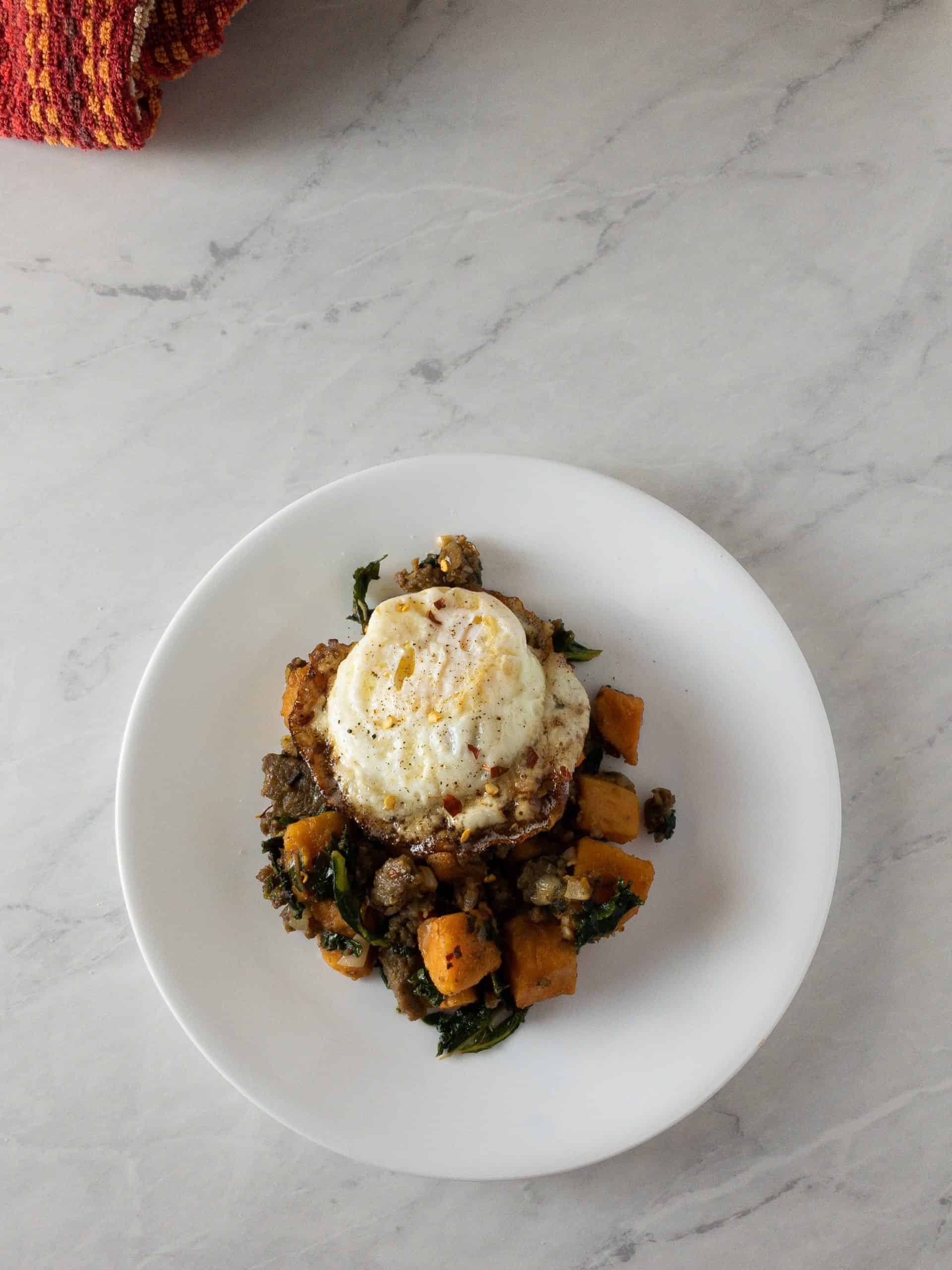 Spicy Sweet Potato Hash topped with a fried egg on a white plate.
