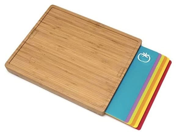 A bamboo wood cutting board with 6 colored plastic cutting mats in various colors.