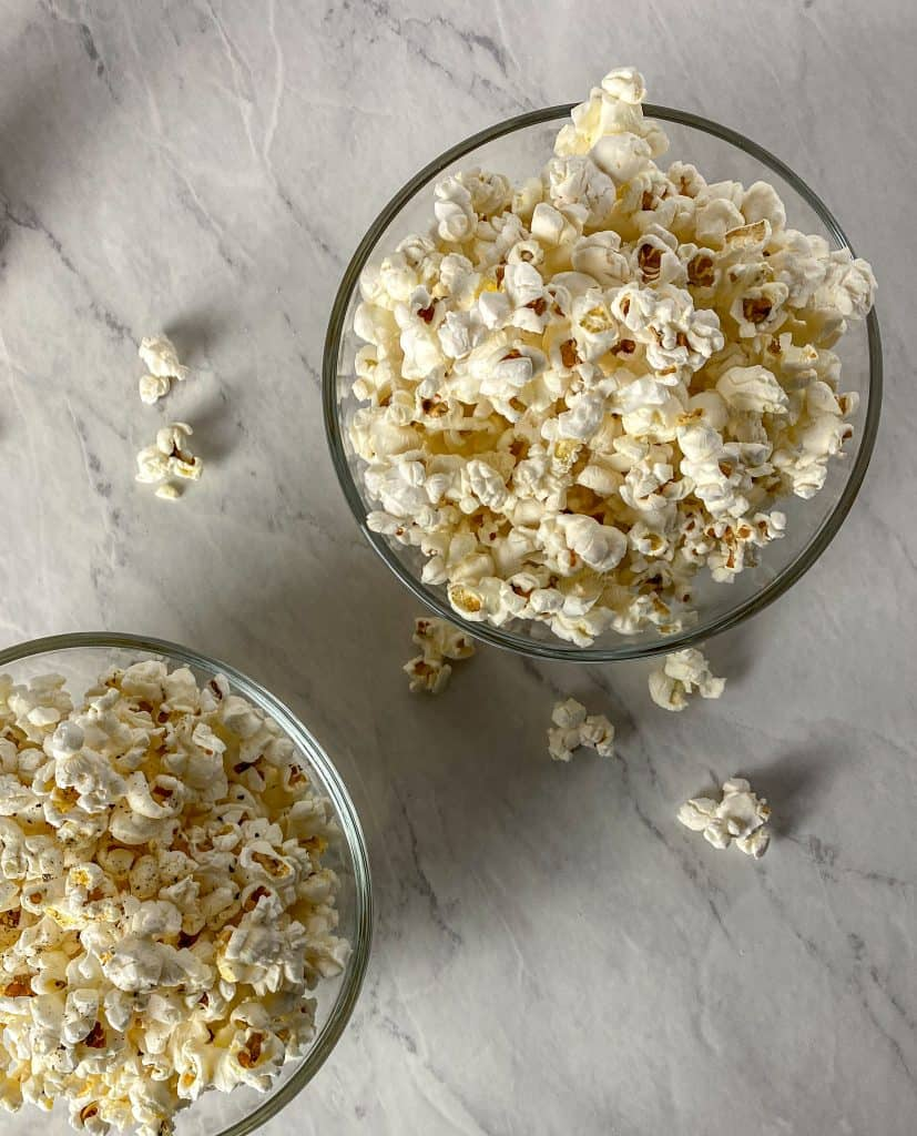 Two glass serving bowls filled with popcorn.