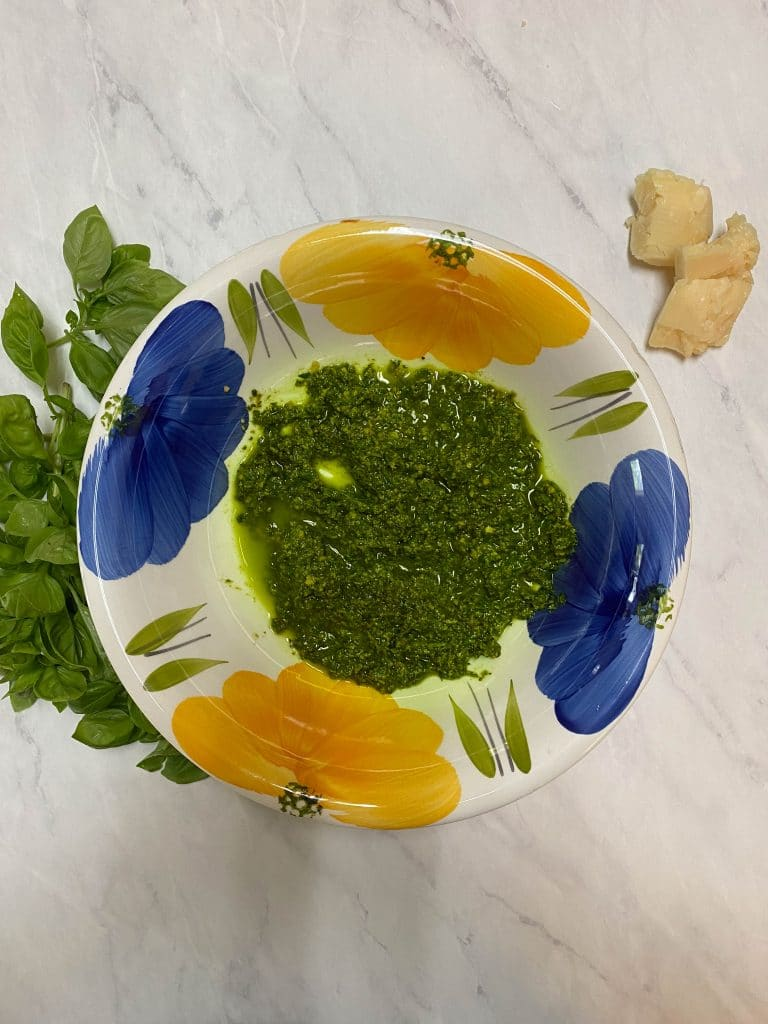 Nut free basil pesto in a white bowl with blue and yellow flowers on it. Basil leaves and parmigiano-reggiano cheese sitting on counter.