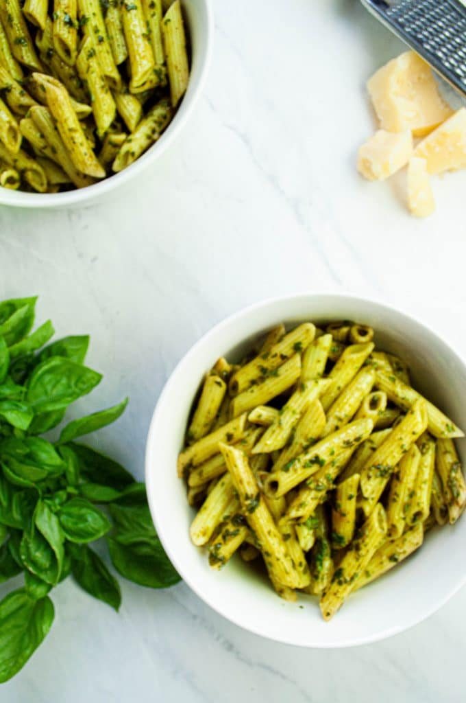 Two white bowls of nut-free basil pesto pasta next to parmigiano-reggiano cheese, a cheese grater, and basil leaves.