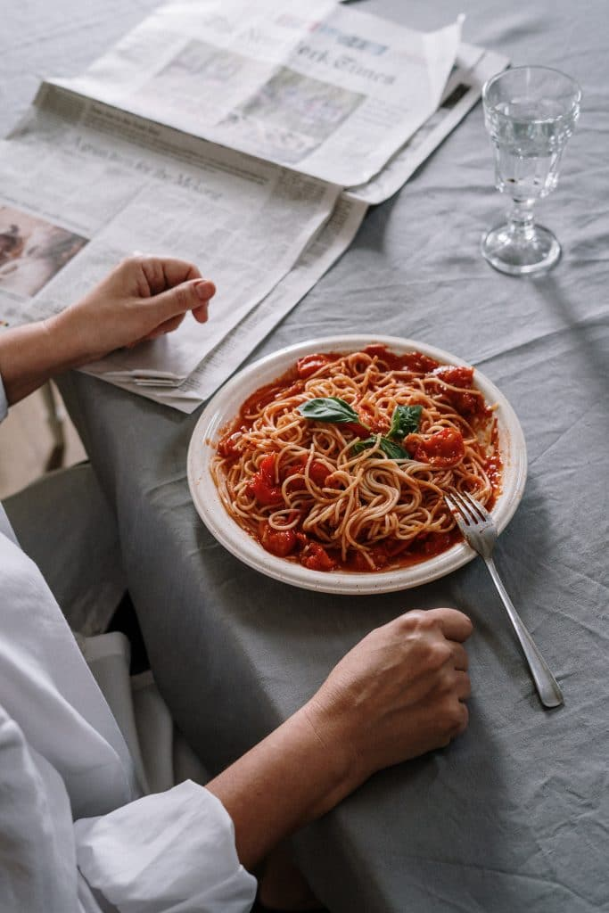 person having a plate of spaghetti for a meal